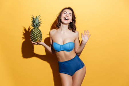 Photo of smiling young woman in swimwear isolated over yellow background holding pineapple. Eyes closed.
