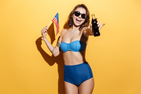 Image of happy young woman in swimwear wearing sunglasses isolated over yellow background. Looking at camera holding USA flag and aerated water.