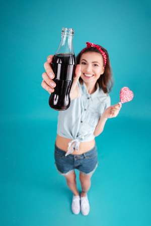 aerated: Image of smiling young lady standing and posing isolated over blue background. Eating candy and holding aerated sweet water. Focus on water. Stock Photo