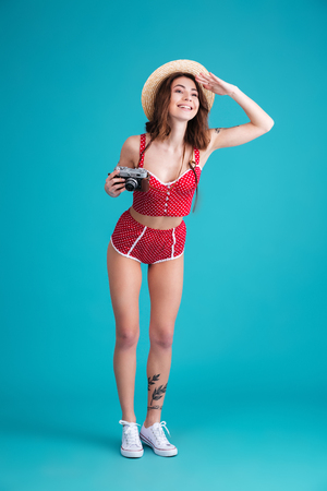 Full length portrait of a smiling happy girl in swimsuit holding retro camera and trying to look far to the side isolated over blue background