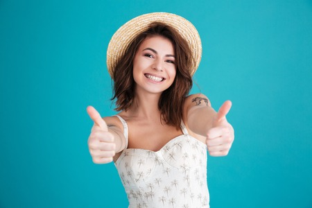 Portrait of a smiling happy young girl in beach hat showing thumbs up gesture isolated over blue background