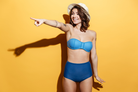Picture of happy young woman in swimwear isolated over yellow background. Looking aside and pointing. Stock Photo