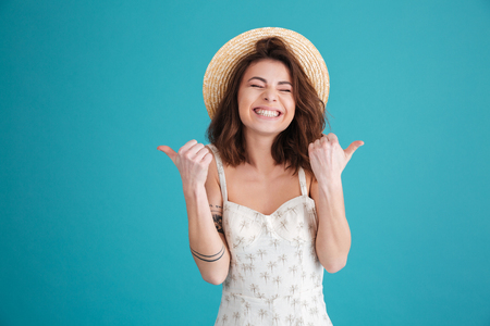 Portrait of a happy young girl wearing straw hat and showing thumbs up isolated over blue background 版權商用圖片 - 80867961
