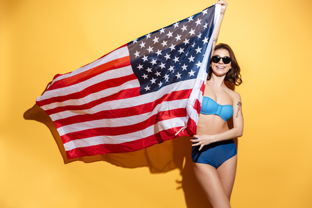 Picture of happy young lady in swimwear isolated over yellow background holding USA flag.