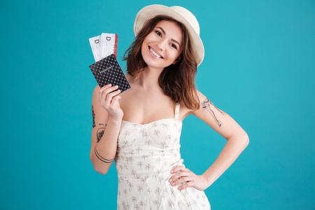 幸せの笑顔の若い女の子で、パスポートを保持して、青い背景に分離されたチケットを旅行の肖像画 写真素材
