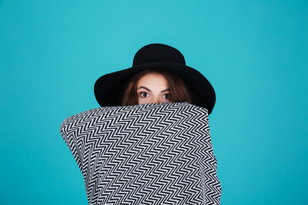 Portrait of a young girl in hat covered in blanket looking at camera isolated over blue background Stock Photo