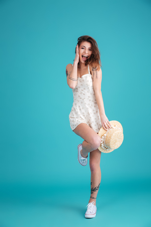 Full length portrait of a playful pretty woman wearing hat and dress posing on one leg isolated over blue background Stock Photo