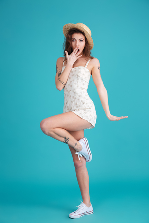 Full length portrait of a playful pretty woman wearing hat and dress posing on one leg and covering mouth with hand isolated over blue background