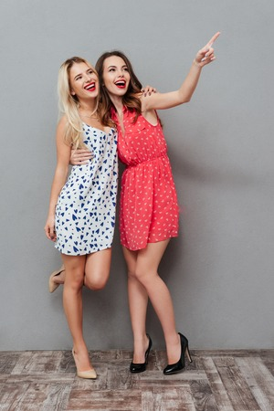 Image of happy young two ladies friends with bright makeup lips standing over grey wall and posing. Looking aside and pointing.