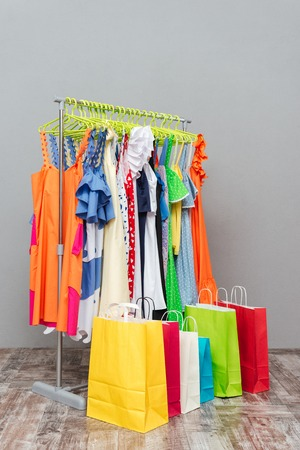 cloakroom: Rack with different colored dresses and packages near it