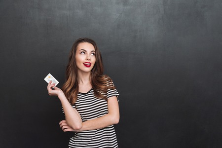 looking aside: Picture of thinking young lady standing over grey wall and holding debit card in hands. Looking aside. Stock Photo