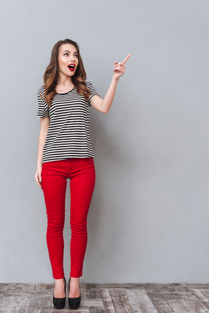 若いの完全な長さの肖像画を驚かせた灰色の背景にスタジオに立っている間指す女性 写真素材 - 80872849