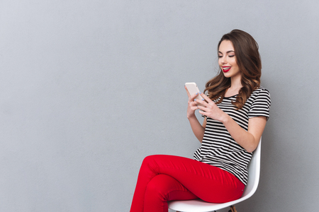 looking aside: Image of happy young lady sitting over grey wall chatting by mobile phone. Looking aside.