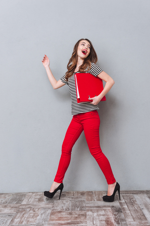 looking aside: Image of smiling young lady walking over grey wall and holding folder. Looking away. Stock Photo