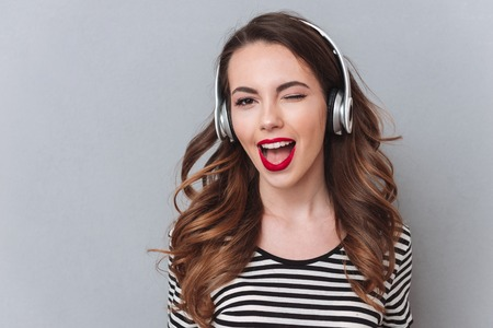 Photo of cute young lady standing over grey wall and listening music with headphones. Looking at camera.
