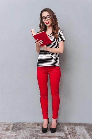 Beeld van gelukkige jonge dame die zich over het grijze boek van de muurlezing bevindt. Opzij kijken. Stockfoto