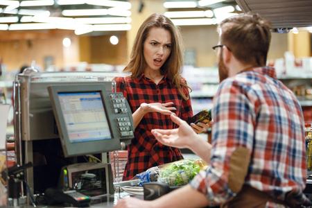 Foto della giovane donna confusa che sta nel negozio del supermercato vicino allo scrittorio del cassiere. Guardando da parte.