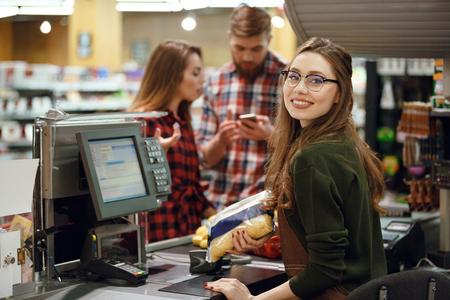 Picture of happy cashier woman on workspace in supermarket shop. Looking at camera. Stock Photo - 80872966