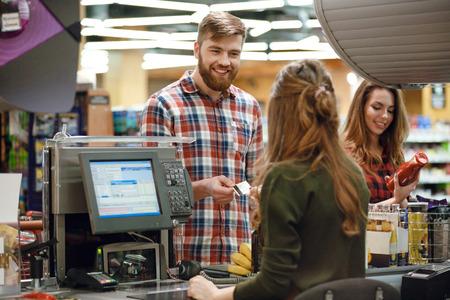 Image de jeune homme joyeux debout dans un magasin de supermarché près du bureau de caisse tenant carte de crédit. En regardant de côté. Banque d'images