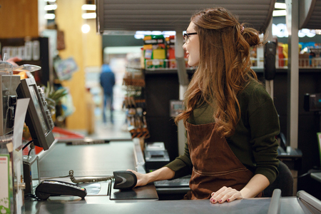 looking aside: Picture of cashier woman on workspace in supermarket shop. Looking aside.