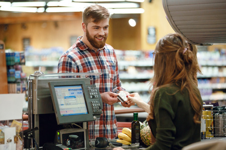 Photo of happy young man standing in supermarket shop near cashier's desk holding credit card. Looking aside.