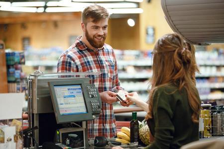 Photo de l'heureux jeune homme debout dans le magasin de supermarché près du bureau de caissier tenant la carte de crédit. Regarde de côté.