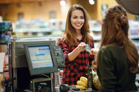 Image of smiling young lady standing in supermarket shop near cashiers desk holding credit card. Looking aside.