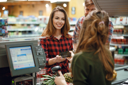 Picture of cheerful young loving couple standing in supermarket shop near cashiers desk. Looking aside. Stock Photo