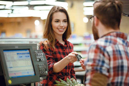 looking aside: Photo of happy young lady standing near cashiers desk in supermarket shop. Looking aside. Stock Photo