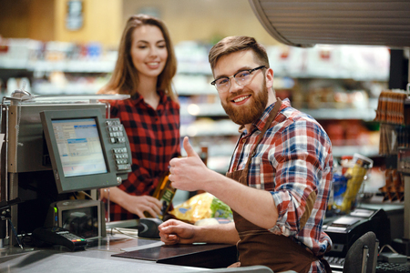 Picture of happy cashier man on workspace in supermarket shop. Looking at camera showing thumbs up. Stock Photo