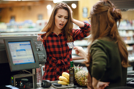 Photo of confused young lady standing in supermarket shop near cashier holding credit card. Stock Photo - 80872995