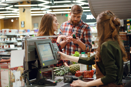 Photo of concentrated young couple standing in supermarket shop near cashier's desk. Looking aside. Stockfoto