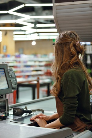 Back view picture of cashier on workspace in supermarket shop.