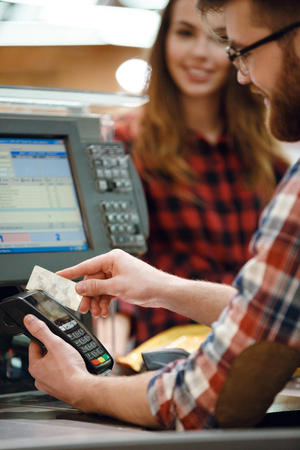 Cropped image of cashier man on workspace in supermarket shop create payment with credit card.