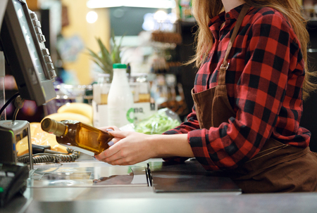 Cropped photo of cashier lady on workspace in supermarket shop.