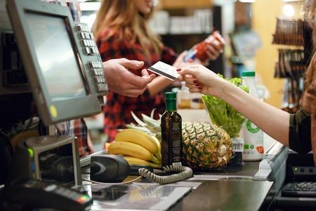 若い男の写真がトリミングされては、スーパー マーケットでワークスペースにレジの女性にクレジット カードを与えます。 写真素材