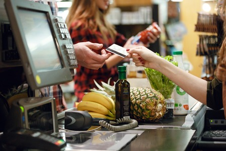 Cropped picture of young man gives credit card to cashier lady at workspace in supermarket.