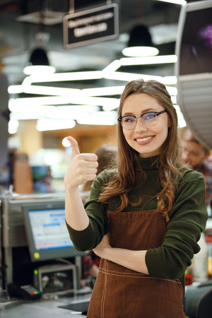 contactless: Photo of happy cashier woman on workspace in supermarket shop. Looking at camera showing thumbs up. Stock Photo