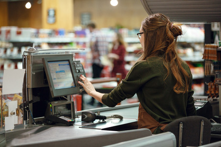 Back view photo of cashier woman on workspace in supermarket shop. Looking aside. Banque d'images