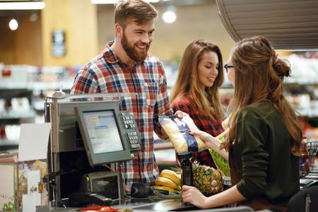 Image de joyeux jeune homme debout dans le magasin du supermarché près du bureau de la caissière. Regardant de côté.
