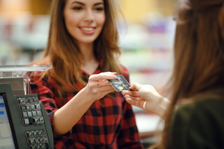 Picture of happy young lady standing in supermarket shop near cashiers desk holding credit card. Focus on card.