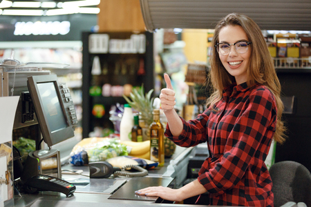Picture of cheerful cashier woman on workspace in supermarket shop. Looking at camera showing thumbs up.