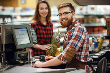 Image of cheerful cashier man on workspace in supermarket shop. Looking at camera.