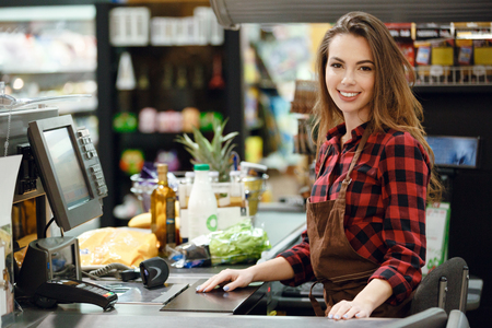 Image of cashier lady on workspace in supermarket shop. Looking at camera. Banco de Imagens