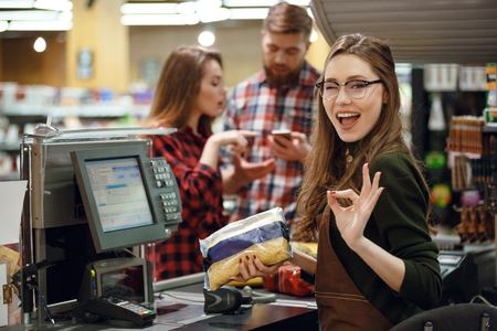 Image of cheerful cashier woman on workspace in supermarket shop. Looking at camera make okay gesture.