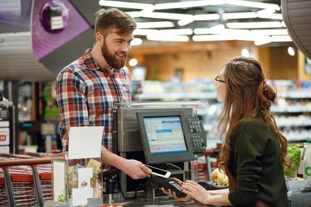 Image de cashier lady sur espace de travail dans le magasin de supermarché créer un paiement avec une application de téléphone mobile.