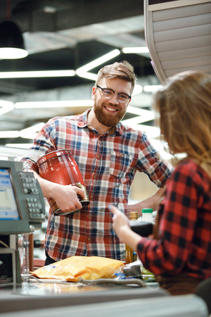 hapy: Photo of happy young man standing near cashiers desk in supermarket shop with beer. Looking aside. Stock Photo