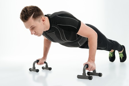 Portrait of a confident healthy sportsman doing push ups with gym equipment isolated over white background