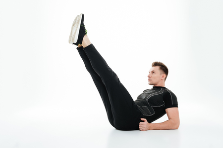 Full length portrait of a serious healthy sportsman doing abdominal exercises on the floor isolated over white background Stock Photo