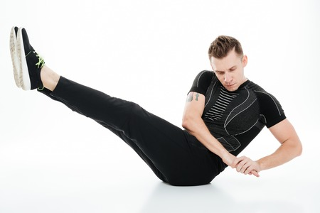 Full length portrait of a concentrated sportsman doing twisted abdominal exercises on the floor isolated over white background